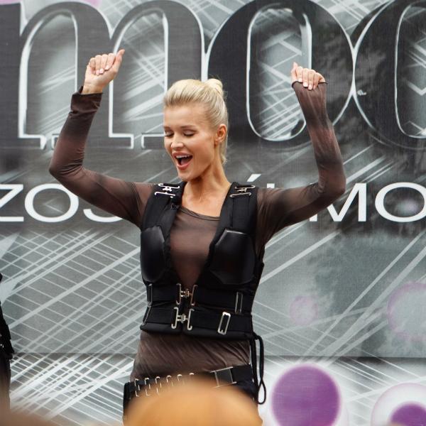 Joanna Krupa unosi ręce w górę w geście radości i zwycięstwa
